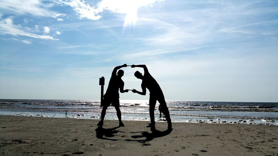 Silhouette Of People Making Finger Frame On Beach
