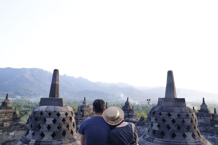 Rear view of couple looking at temple against clear sky