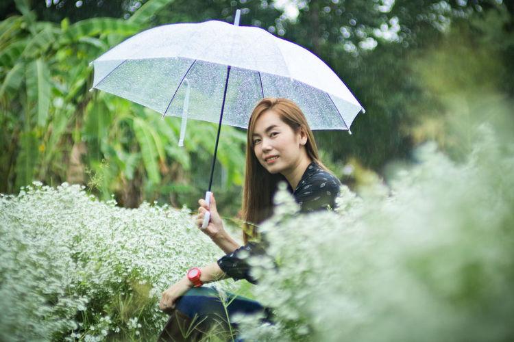 Full length of woman with umbrella in rain