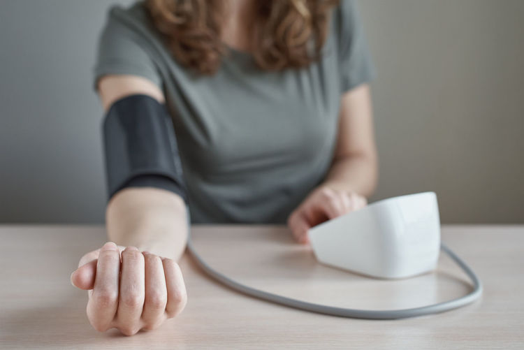 Midsection of woman measuring blood pressure with gauge on table
