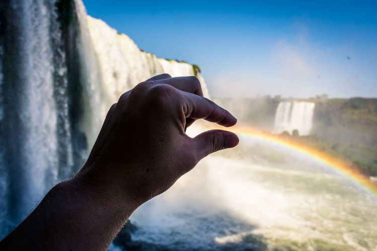 Close-up of human hand against rainbow in sea