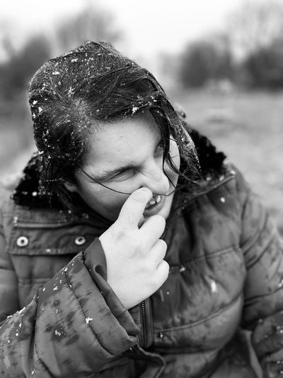 Close-up of teenage girl with hand on nose during winter