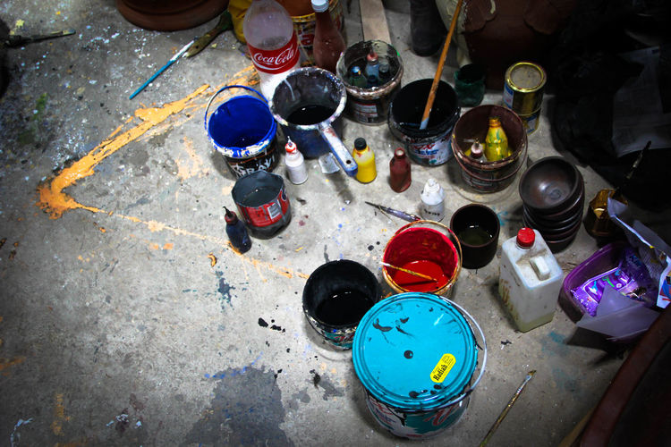 High Angle View Of Paint Cans And Containers On Floor