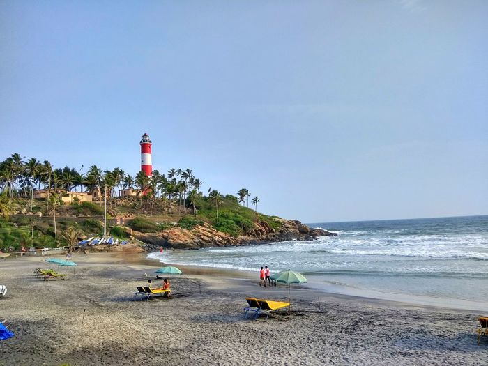 Kovalam Beach Beach Sand Sea Flag Incidental People Outdoors Sunny Day Lifeguard  Horizon Over Water Sky Vacations Summer Travel Destinations Water Nature Adults Only Clear Sky People Beauty In Nature India Kerala Travel Tourist Destination Light House Beach