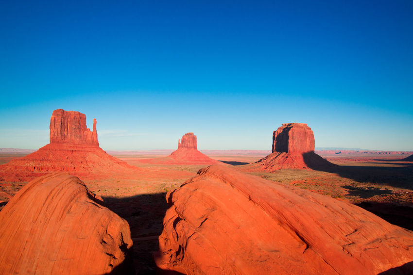 the majestic sandstone masterpieces in the Navajo Nation's Monument Valley Park Adventure Arid Climate Beauty In Nature Blue Clear Sky Day Desert Environment Landscape Mesa Monument Valley National Park National Parks Nature Navajo Nation No People Outdoors Park Rock - Object Sand Scenics Sky Sunlight Tourism Travel