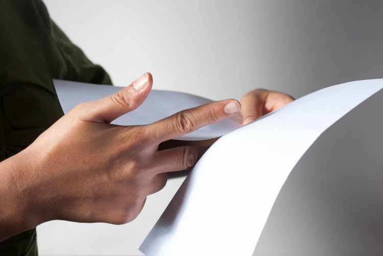 Close-Up Of Human Hands Holding Blank Papers Against White Background