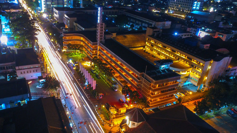 High angle view of illuminated street amidst buildings at night