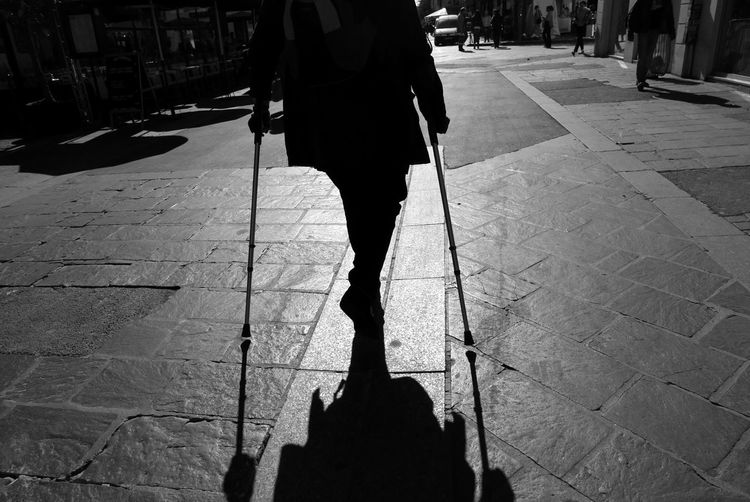 Low section of disabled man walking with cane on footpath