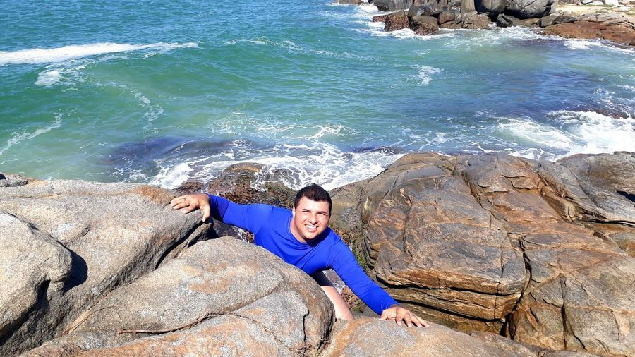 High angle portrait of man on rock against sea