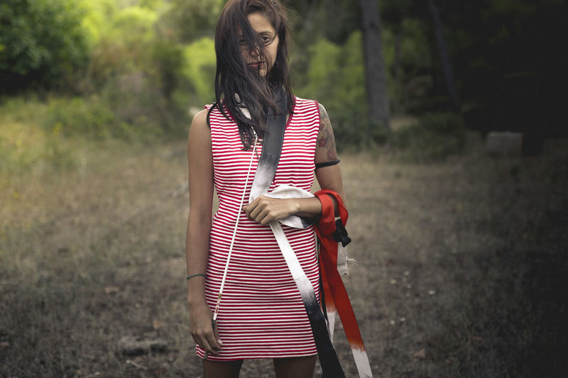 Portrait Of Young Woman Holding Belts Standing On Field