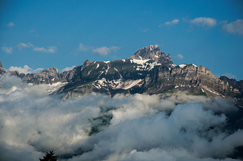 View of snowy peaks with alpine mountains landscape and clouds in saint-gervais-les-bains, france.