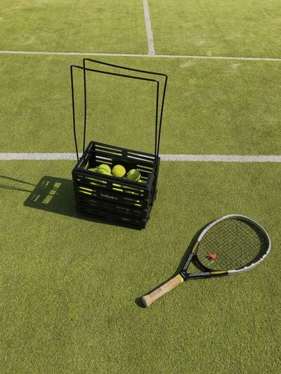 High angle view of tennis balls and racket on playing field