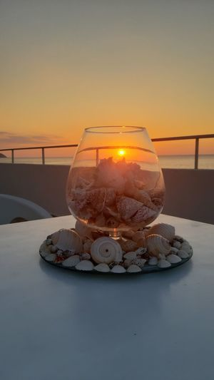 Close-up of shells on table against sky during sunset