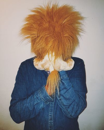 Person Covering Face With Stuffed Toy While Standing Against Wall
