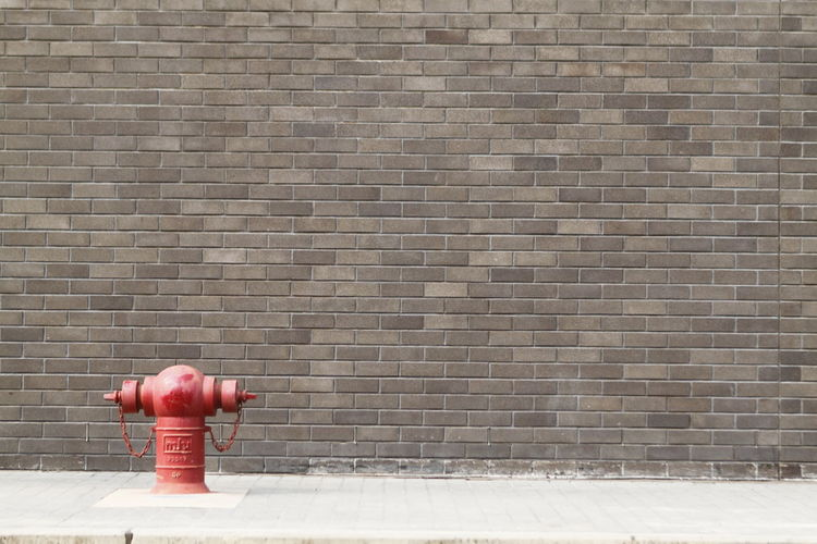 Red fire hydrant on footpath against brick wall