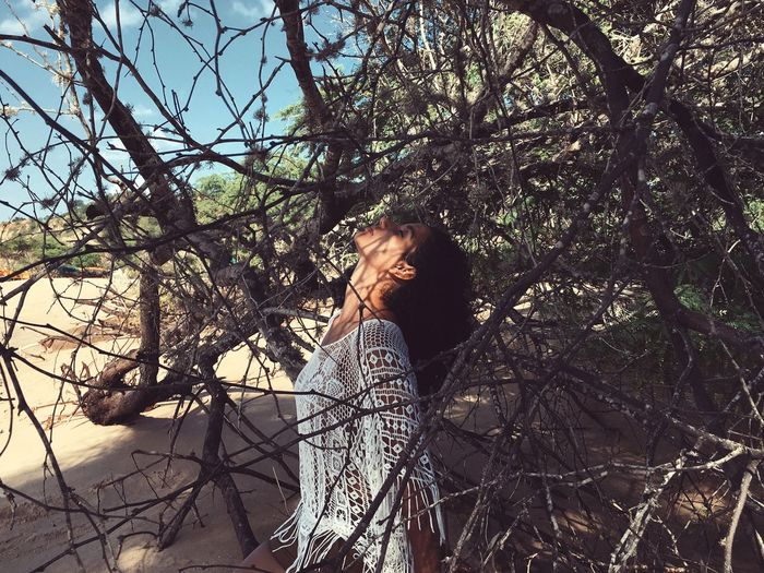 Side View Of Young Woman With Eyes Closed Standing By Fallen Tree At Beach