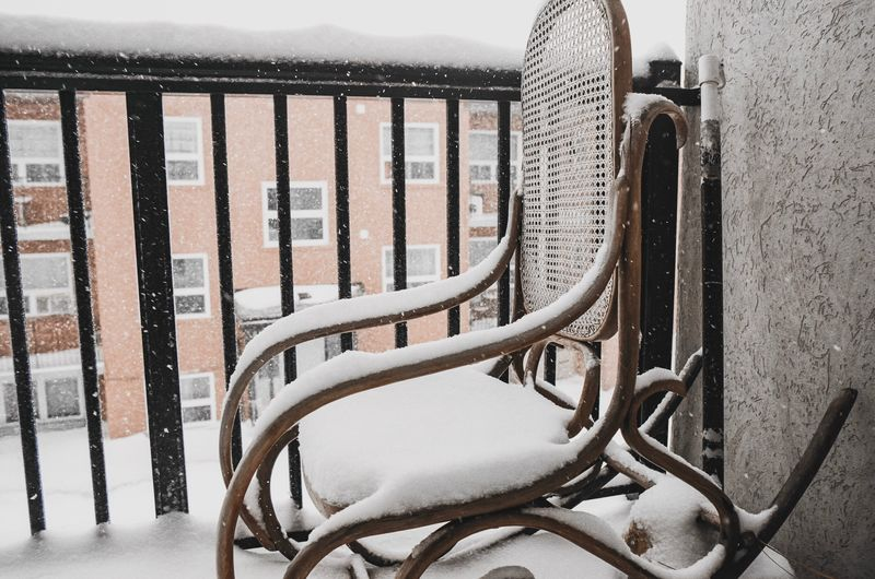 Close-up of railing against snow covered wall