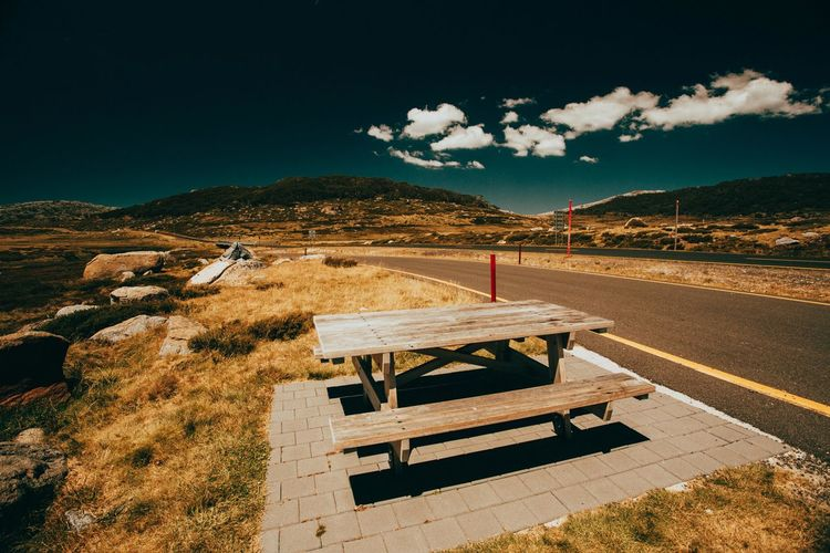 Empty picnic table and bench on roadside against sky