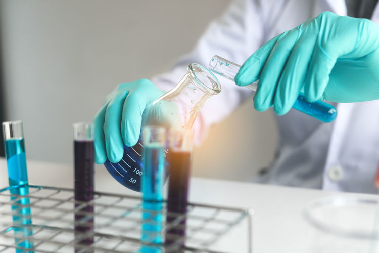 Midsection Of Scientist With Chemicals At Laboratory