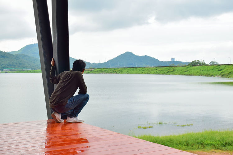 Woman sitting on mountain by lake against sky