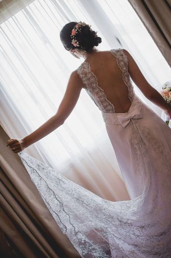 Rear view of bride standing by window