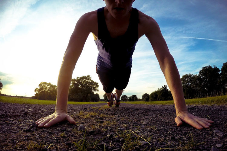 Low Section Of Man Exercising On Road During Sunset