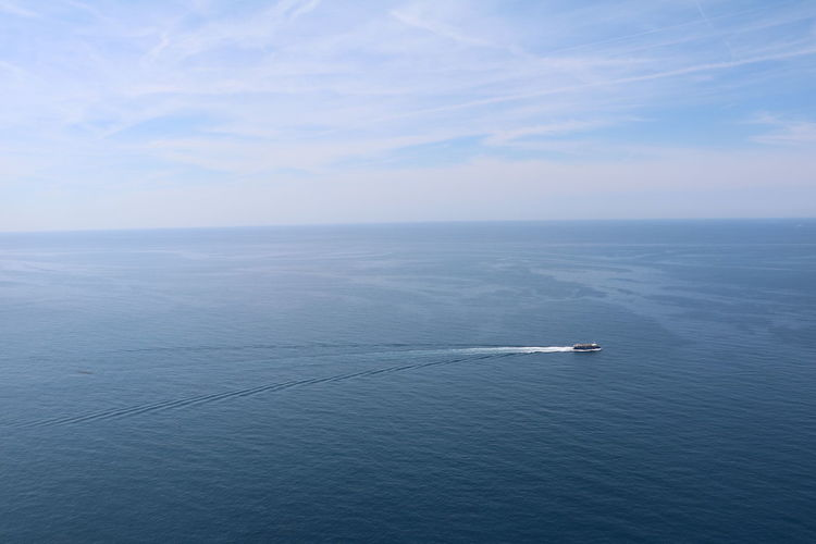 Landscape of a boat speeding along the ocean water in Cinque Terre, Italy Bright Cinque Terre Daytime Nature Speed Boat Speeding Travel Blue Boat Clean Clear Clouds Destination Expanse Horizon Italy Landscape Lone Merge Monochrome Movement Sea Single Sky White