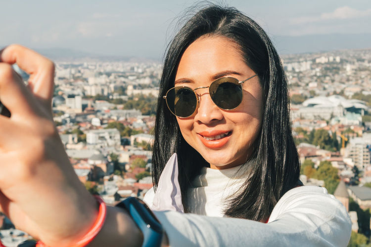 Portrait of smiling woman with cityscape against sky