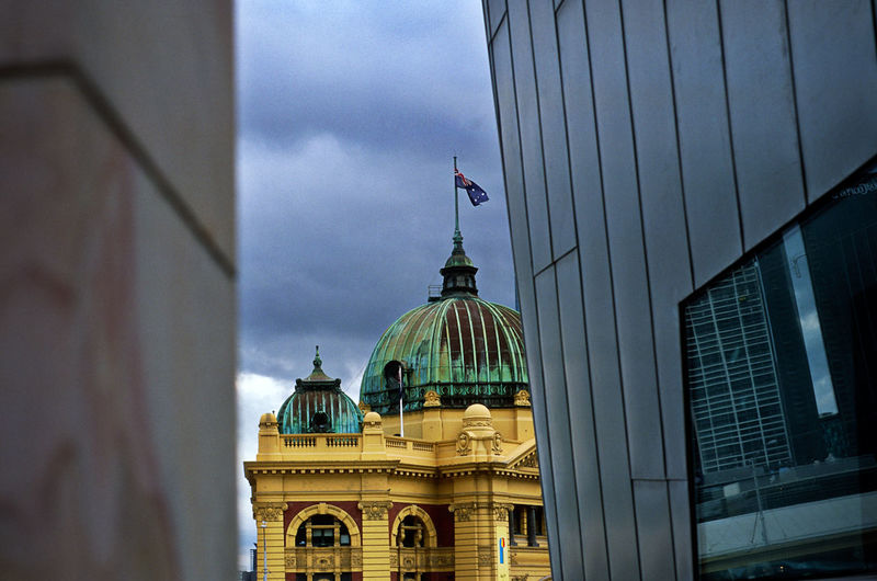 Exterior of old government building with australian flag against cloudy sky