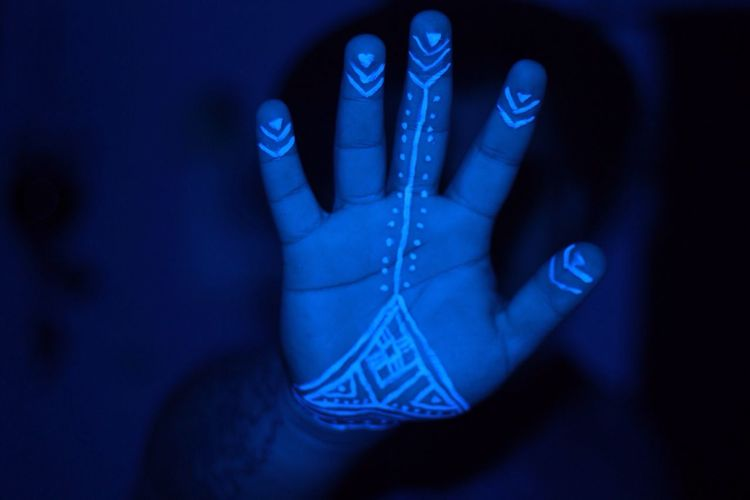 Cropped Image Of Hand With Henna Tattoo In Darkroom