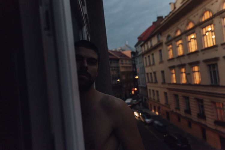 Portrait of shirtless man standing in city