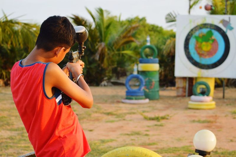 Rear view of boy aiming paintball gun on target against trees