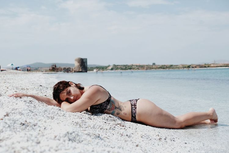 Young woman lying on sand at beach against sky