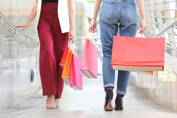 Low Section Of Females With Shopping Bags Walking In Corridor