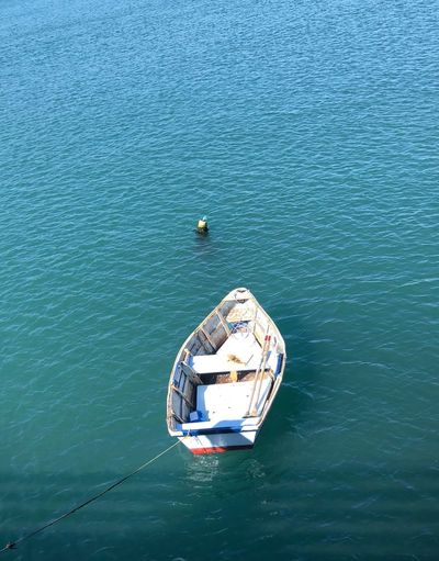 Lonely boat in turquoise waters Wood Boat Boat Water Nautical Vessel High Angle View Transportation Mode Of Transportation Waterfront Sea Day Blue Scenics - Nature No People