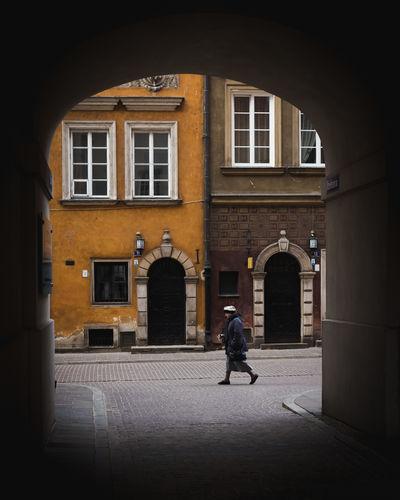 Rear view of man walking on street against building