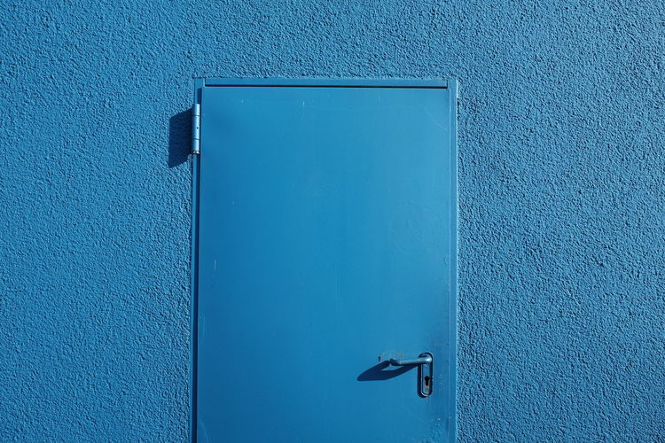 Close-up of closed door on blue wall