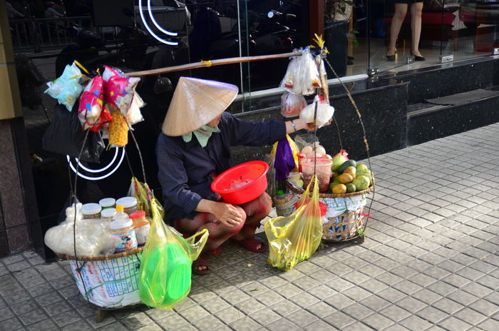 STREET PEDDLER IN HO CHI MINH CITY Asian Style Conical Hat Day Food Food And Drink Occupation Outdoors People Plastic Bag Real People Retail  Sitting Street Peddler Women