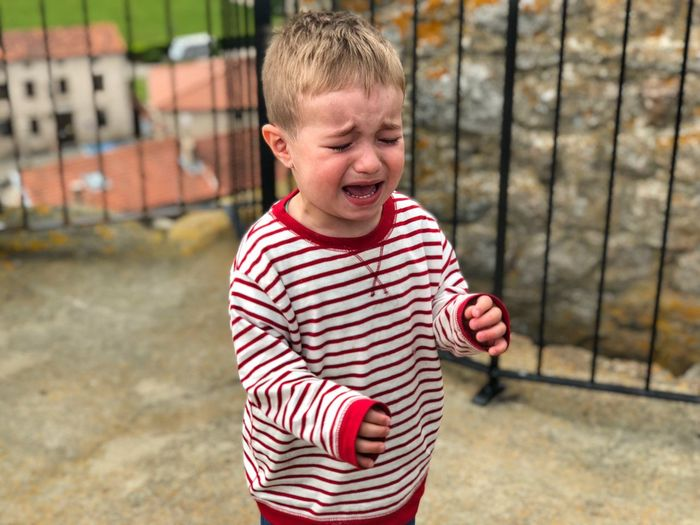 Boy crying while standing on footpath