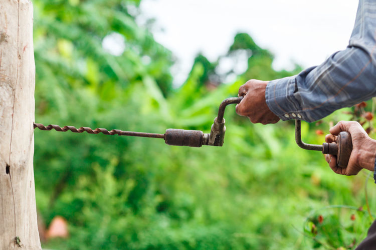 Close-up Day Focus On Foreground Gardening Green Color Hand Holding Human Body Part Human Hand Men Metal Nature One Person Outdoors Plant Real People Rope Stick - Plant Part Tree Work Tool Working