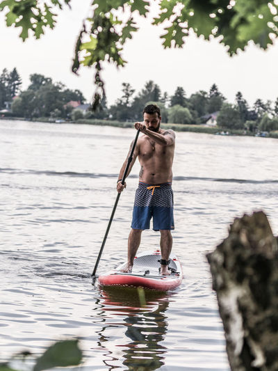 Casual Clothing Day Full Length Holding Lake Leisure Activity Lifestyles Men Nature One Person Outdoors Plant Real People Shirtless Shorts Standing Tree Water