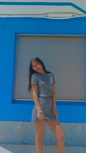 Full length of smiling young woman standing against blue wall