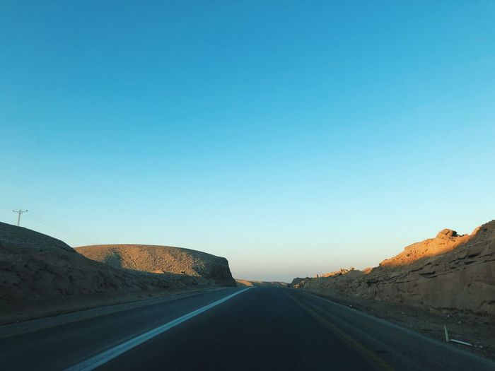 Road at desert against clear blue sky during sunset