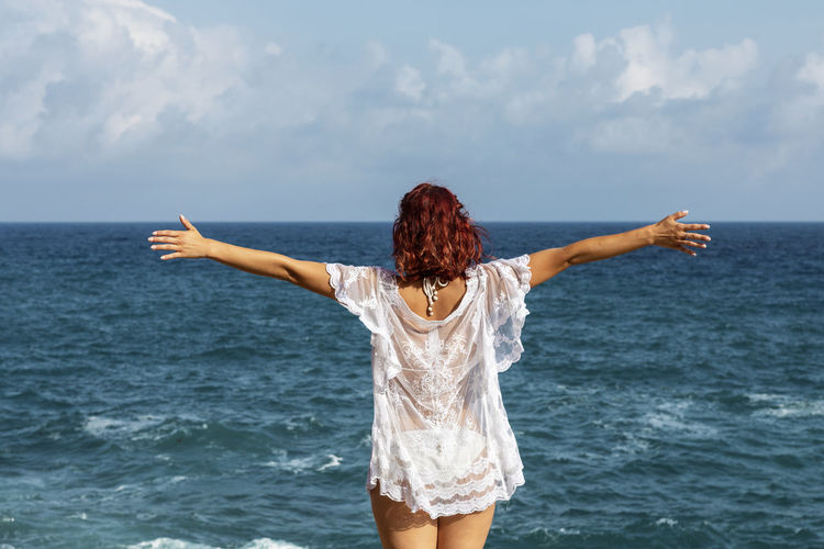 young woman spreading her arms, looking at the ocean Water Sea Rear View Sky Beauty In Nature Leisure Activity One Person Lifestyles Real People Hairstyle Standing Three Quarter Length Scenics - Nature Long Hair Arms Outstretched Human Arm Women Hair Nature Horizon Over Water Limb Arms Raised Outdoors Mallorca Mediterranean