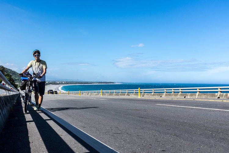 Man walking with a sports bicycle at the roadside on the bridge