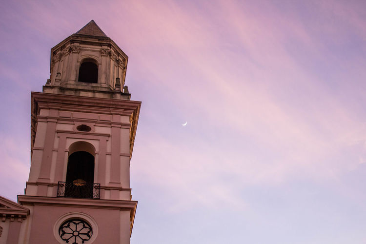 Low angle view of bell tower against sky during sunset