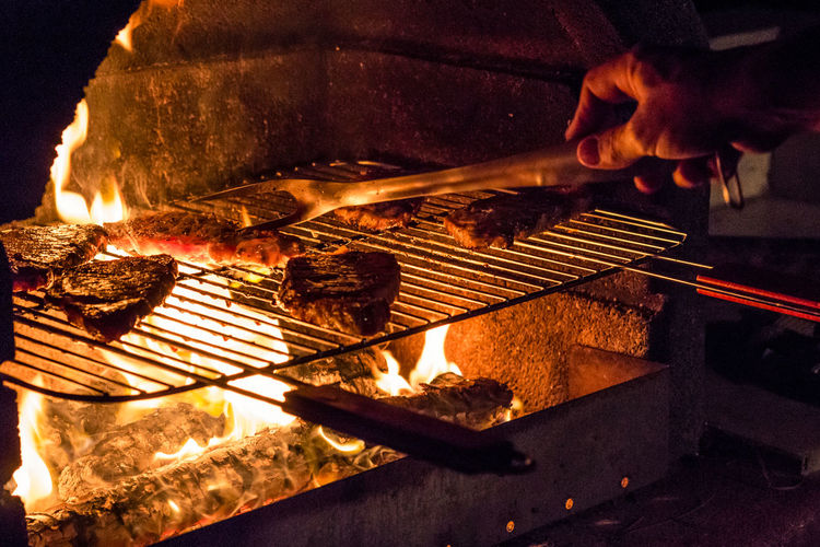 Cropped image of person hand cooking meat on barbecue grill