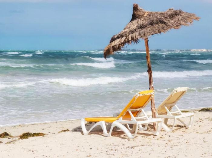 Deck chair on shore at beach against sky