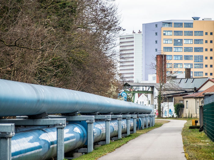 District heating pipes District Heating Pipes Architecture Built Structure Building Exterior Tree Plant City Day Building Nature Pipe - Tube Outdoors No People Residential District Connection Transportation Pipeline Blue In A Row Street Sky Energy Supply Infrastructure