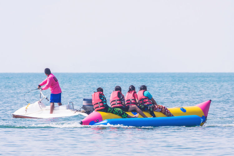 Man on jet boat by women rafting in sea